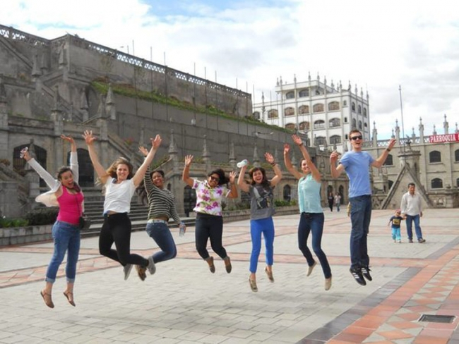 Seven students of different genders and ethnicities are jumping with their arms outstretched in the center of a city square.